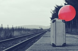Old suitcase with a red balloon at the train station with retro effect