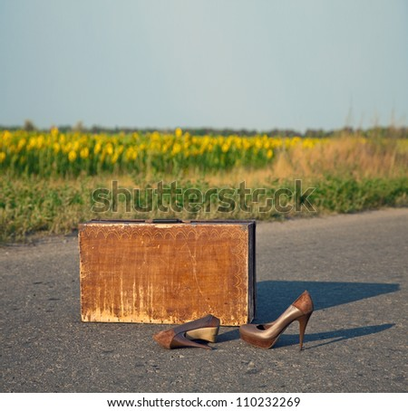 Old suitcase with brown shoes left on dirt road