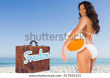 Old suitcase with the message freedom against pretty woman smiling and holding a beach ball #417842155