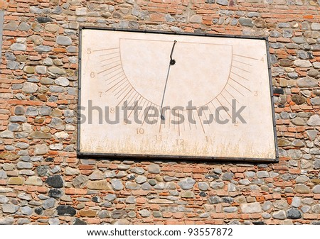 old sundial on a red bricks wall