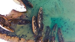 Old sunken ships near coast in winter. Footage. Top view of graveyard of ships in turquoise water off snowy coast in winter. Sunken ships near shore with turquoise winter water