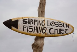 old surf board nailed on wooden pole with painted text direction information, surfing lesson and fishing cruise