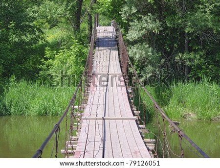 Old suspension walk bridge across river in the  forest #79126051