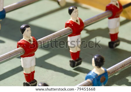 old tabletop with red football player in toy - stock photo