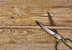 old tailor scissors and rope on the wooden background