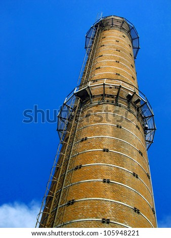 old tall brick chimney on blue sky background