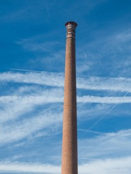 Old tall chimney made of bricks. long and thin clouds in the sky. Vertical