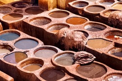 Old tannery in Fez, Morocco. The tanning industry in the city is considered one of the main tourist attractions. The tanneries are packed with the round stone wells filled with dye.