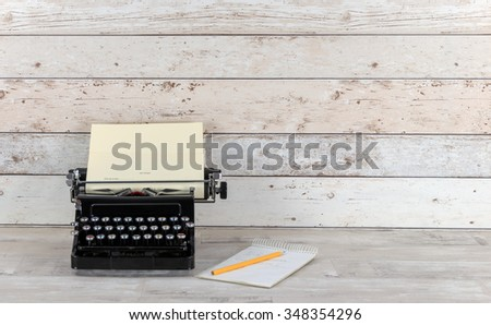 Old Technology, typewriter with notepad and  pencil on an old shabby wood effect desk and background