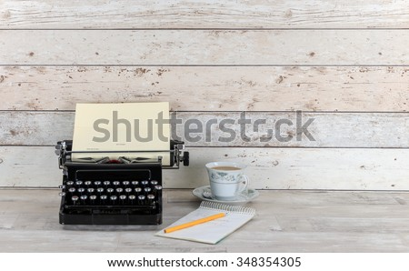Old Technology, typewriter with notepad, pencil and cup of tea on an old shabby wood effect desk and background