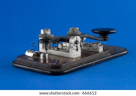 Old telegraph key over blue background