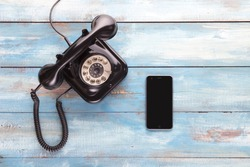 Old telephone and mobile phone on a blue wooden board