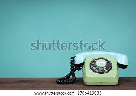 Old telephone on wooden table in front of green background. Vintage phone Stockfoto ©