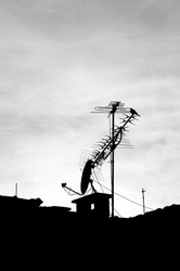 old television antennas and dish antenna silhouettes on the roof