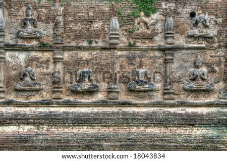 Old temple wall in Thailand with Buddha figures