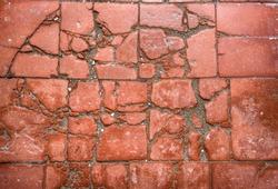 Old terracotta cracked and broken tiled floor.