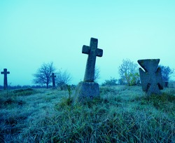Old terrible stone cross on cemetery on background of sky