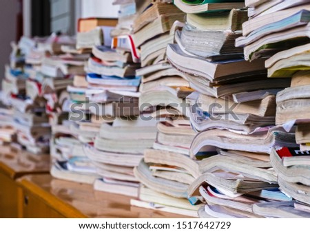 Old textbooks that were useful for the education of several generations of students lay on a shelf inside a school. Narrow depth of field image, focus centred on closer books.
