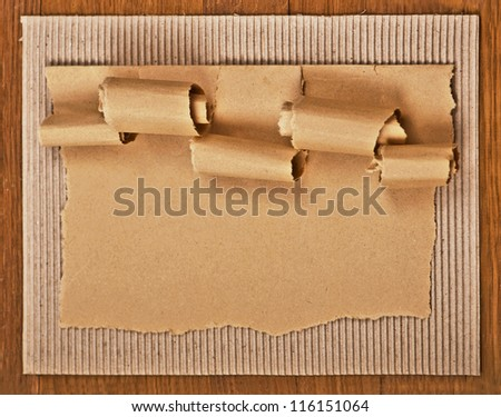 old textured cardboard sheet with torn edges wooden background