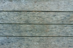 Old textured discoloured wooden boards arranged horizontally.