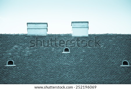 Old tiled roof with chimneys and dormers on blue sky background. Toned. #252196069