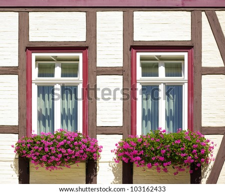 Old timber frame-work house with windows and flower-boxes - Some old timber frame-work house with windows and flower-boxes using the example of a townhouse in Wernigerode, Germany, Europe.