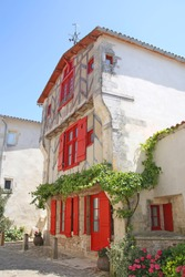 Old timbered red house with shutters and other historical buildings in Ile de Re, Charente Maritime, France.