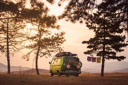 Old timer camper van parked on the top of the hill between pine trees in the beautiful sunset sky
