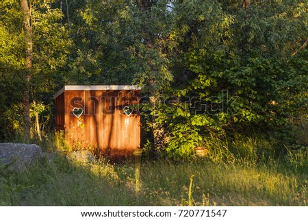 Old times outdoor dry toilet, outhouse, privy in red. Bushy environment.