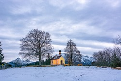 Old tiny church sitting alone on a hill in the middle of the bavarian alps. Two big trees surround it. Snowy mountaintops surround the valley in which the chapel sits. Cloudy snowy white sky.