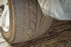 Old tire with worn tread and scratch, worn old car tire tread with damaged, scratch, worn tire tread in the car wheel