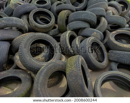 Old tires.A lot of Wheel Tires dumped in a landfill.used car tires pile in the tire repair shop yard.Tyre dump.Industrial landfill for the processing of waste tires and rubber tyres.