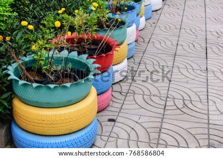 Old tires that are painted in assorted colors and used for a flower planter.