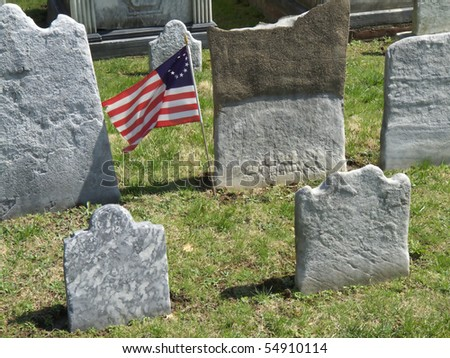 old tombstones with no inscription left with an american flag