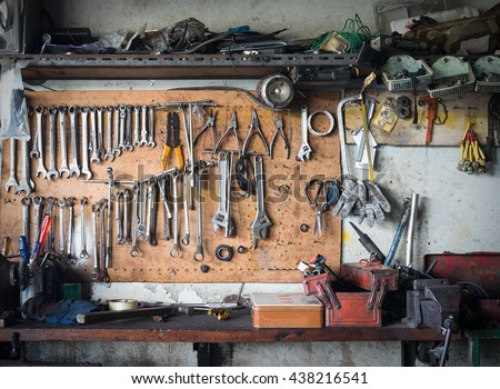 Old tools hanging on wall in workshop , Tool shelf against a wall