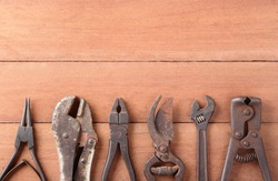 old tools on wood background with space for text or image / cerclip pliers, locking pliers, pliers, pruning shears, adjustable wrench, end cutting pliers