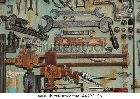 Old tools, wrenches, scissors and a rusty machine on the wall of the garage