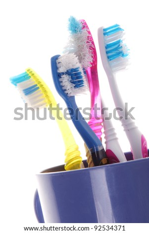 old toothbrushes in a blue glass on white background