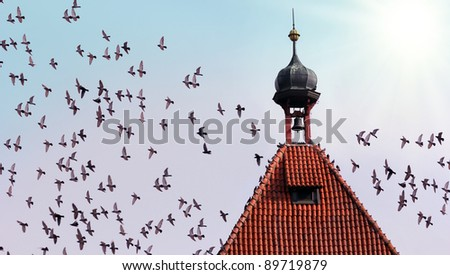 old tower with bell and many flying birds