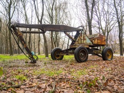 old towing forestry crane used for harvesting logs