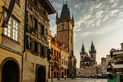Old Town Square in Prague, Czech Republic. Empty city during sunrise without people surrounded by historical, gothic style buildings and the famous Astronomical Clock Tower.Beautiful urban scene