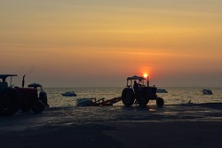 Old tractor is loading a tourist boat at sunset.Pattaya, Thailand