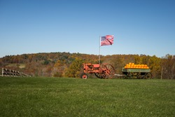 Old tractor pulling a wagon full of pumpkins, while flying The American Flag. Near Meadows of Dan.