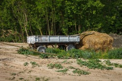 Old tractor trailer and a pile of straw in the village yard