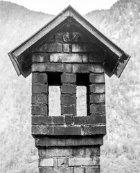 Old traditional chimney in the shape of a small house with roof and windows. Unusually shaped  chimney with multiple openings and a roof.