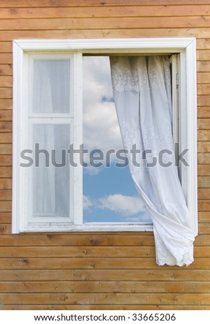 Old traditional country-style window in a wooden house (with the blue sky and white clouds in the window)