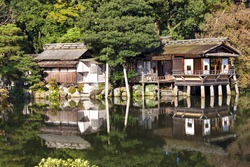 Old traditional Japanese tea houses on the edge of garden lake with reflections in the water, pine trees . Autumn scene .