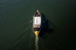 Old traditional portuguese boat, in Porto, with passengers on board plying the Douro river, in Portugal, aerial view