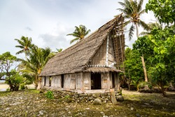 Old traditional thatched yapese men's meeting house faluw (fale), on an elevated limestone platform foundation. Shore of South Pacific ocean. Yap island, Federated States of Micronesia, Oceania.