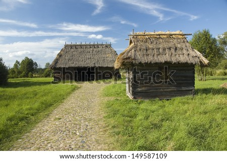 Old, traditional wooden buildings with thatched roofs in a village in Bialowieza, Poland - stock photo